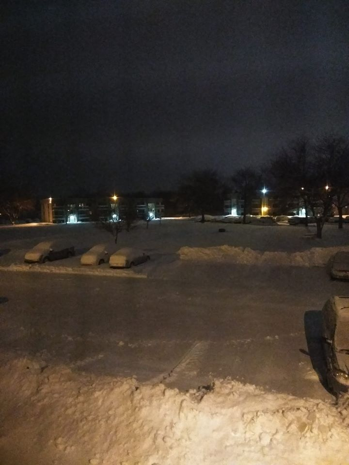The parking lot at the Southwind Apartments shows cars covered in a thick blanket of snow late Friday night after Winter Storm Mateo.